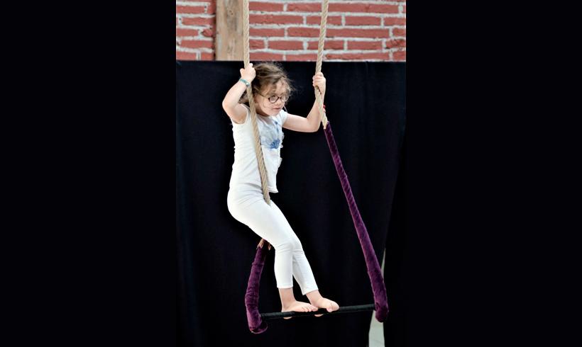 Petite fille debout sur un trapèze