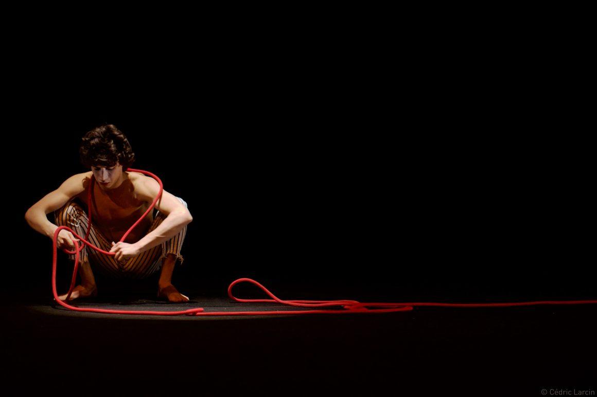 Garçon sur scène avec cordelette rouge